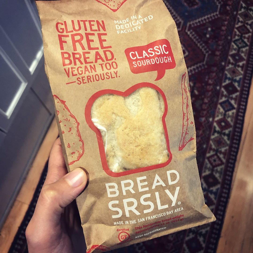 """SRLY though, we all want a little bread in our life. For those of us that have sworn off wheat, here comes a worthy alternative @breadsrsly. Made in SF, found at local grocers and shipping via the webs. Super impressed with the taste and texture. I toast and add Vegan Cream Cheese (post coming soon!) + Corsican honey + @numiorganictea Rooibos Chai. . Comes in Classic Sourdough and varieties like Sweet Onion. I prefer the dinner rolls over the loaves...more crust! 🙃 . ️ Gluten-free, Dairy-free (Vegan), Delicious, Satisfying texture, Organic, Non-GMO, handmade Gluten-free grains (rice, millet, sorghum), Added Starch (arrowroot), Xanthan Gum None . P.S. There isn't usually a huge hole in the middle of the loaf, but that's what happens with handmade food! When I cut it, I actually yelled """"SRLY?!""""🤪 . . . . . #Glutenfree #Dairyfree #GFDF #Vegan #bread #seriously #breadsrly #handmade #sourdough #grains #wheatfree #snacks #treats #vegancheese #creamcheese #numi #numitea #tea #chai #organic #local #SanFrancisco #BayArea #DrNatashaF #KANARILife #HealthyJunks #HJapproved"""